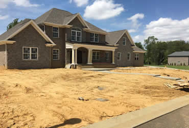 New construction photo of home before flower beds, much, planting and power seeding yard
